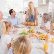 Family looking at the mother with a turkey plate — Stock Photo #24101117