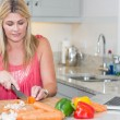 Woman making recipe from internet on laptop in kitchen - Stock Photo