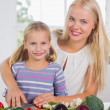 Smiling mother teaching cutting vegetables - Stock Photo