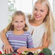 Stock Photo: Smiling mother teaching cutting vegetables