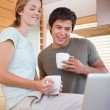 Couple using laptop while drinking coffee - Stock Photo
