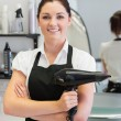 Confident female hairdresser holding hair dryer — Stock fotografie