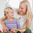 Stock Photo: Mother teaching cutting vegetables