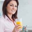 Smiling young woman with orange juice — Stock Photo