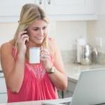 glückliche Frau mit Laptop und Kaffee Tasse Bereitschaftsdienst in Küche — Stockfoto
