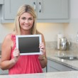 Portrait of casual woman holding digital tablet in kitchen — Stock Photo #24102325