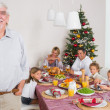 Smiling grandfather standing at the dinner table — Stock Photo