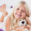 Little girl with her teddy bear lying on a bed — Stock Photo