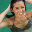 Pretty woman touching her hair in pool — Stock Photo