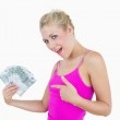 Portrait of happy woman pointing at fanned euro banknotes — Stock Photo #24103099