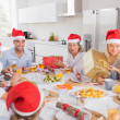 Stock Photo: Smiling family around dinner table at christmas