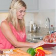 Woman reading cookbook book while cutting vegetables in kitchen — Stock Photo