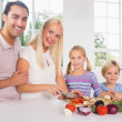 Smiling family cutting vegetables together — Stock Photo