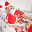 Happy family exchanging christmas gifts - Stock Photo