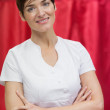 Hairdresser with arms crossed against red curtain — Stock Photo