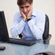 Young worried business man sitting at office desk — Stock Photo