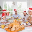 Happy family wearing santa hats around the dinner table — Stock Photo