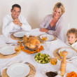 Family smiling around a roast dinner - Lizenzfreies Foto
