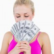 Woman holding fanned banknotes in front of face with eyes closed — Stock Photo