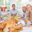 Focus on the roast turkey in front of family - Stock Photo