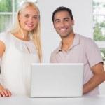 Smiling couple using laptop — Stock Photo #24104613