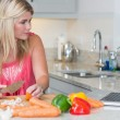 Woman cooking whilst looking at laptop — Stock Photo