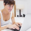 Pretty woman using laptop in bed — Stock Photo #24108917