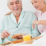 Couple enjoying breakfast in bed — Stock Photo