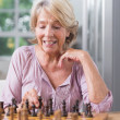 Mature woman playing chess — Stock Photo