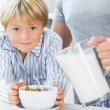 Stock Photo: Father pouring milk for sons cereal