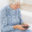 Elderly cheerful womusing smartphone — Stock Photo #24109299