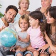 Happy family looking at globe — Stock Photo