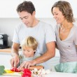 Mother watching father teaching son to chop vegetables — Stock Photo