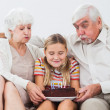 Royalty-Free Stock Photo: Little girl and grandparents blowing out the candles