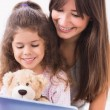 Stock Photo: Happy mother and daughter using tablet pc
