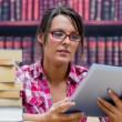 College student using digital tablet with stack of books at libr — Stock Photo #24109705