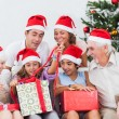 Family watching little girl opening christmas present — Stockfoto