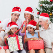 Family watching little girl opening christmas present - Stock Photo