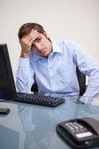 молодой напряженной деловой человек, сидя на офисном столе — Стоковое фото