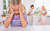 Little girl looking depressed in front of fighting parents — Photo