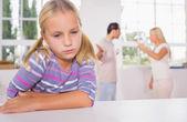 Liten flicka ser ledsen framför kämpar föräldrar — Stockfoto