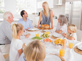 Family looking at the mother with a turkey plate — Stock Photo