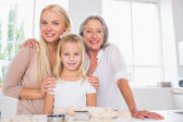 Cheerful mothers and daughters cooking together — Stock Photo