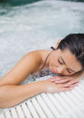 Woman resting at edge of jacuzzi — Stock Photo