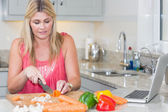Kobieta co przepis z internetu na laptopie w kuchni — Zdjęcie stockowe