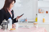 Business woman text messaging while having breakfast in kitchen — Stock Photo