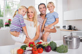 Children in their parents arms in the kitchen — Stock Photo