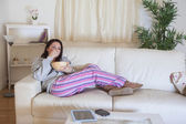 Relaxed woman sitting on couch with bowl at home — Stock Photo