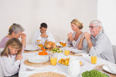 Family saying grace before eating a turkey — Stock Photo