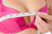 Woman measuring chest in pink bra — Stock Photo